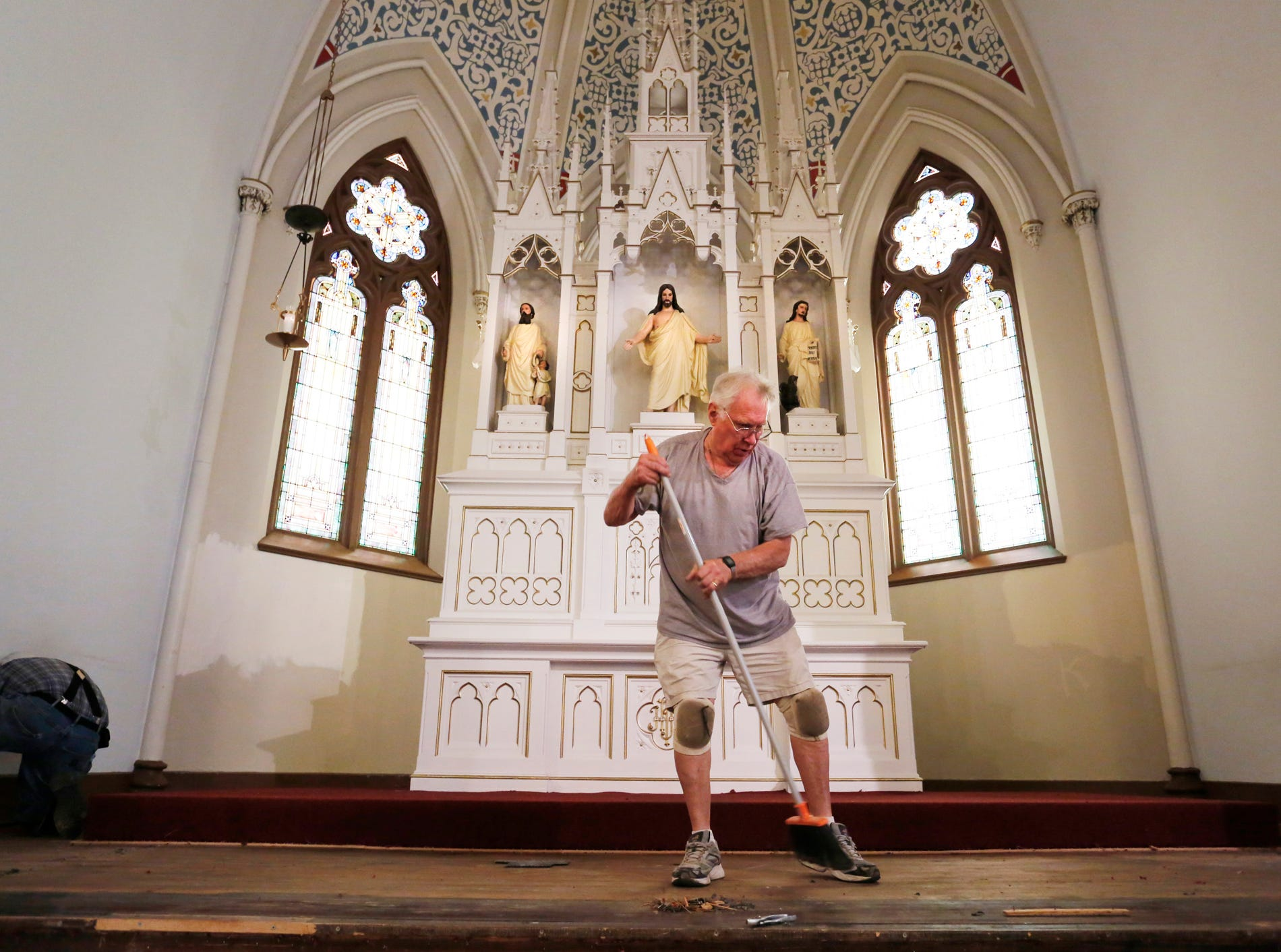 "Irv Dieterle sweeps up debris at the altar as restoration work takes place inside St. James Lutheran Church Monday, July 9, 2018, in Lafayette. About 30 members of the congregation are helping out with the work taking place inside the sanctuary of the church. ""We restored the roof and exterior walls the last two years, and now we're working on the inside,"" said Julie Grott. ""Hopefully we'll be back in here by mid-November,"" Grott said. Services are being held in the school cafeteria while the restoration work is being completed."