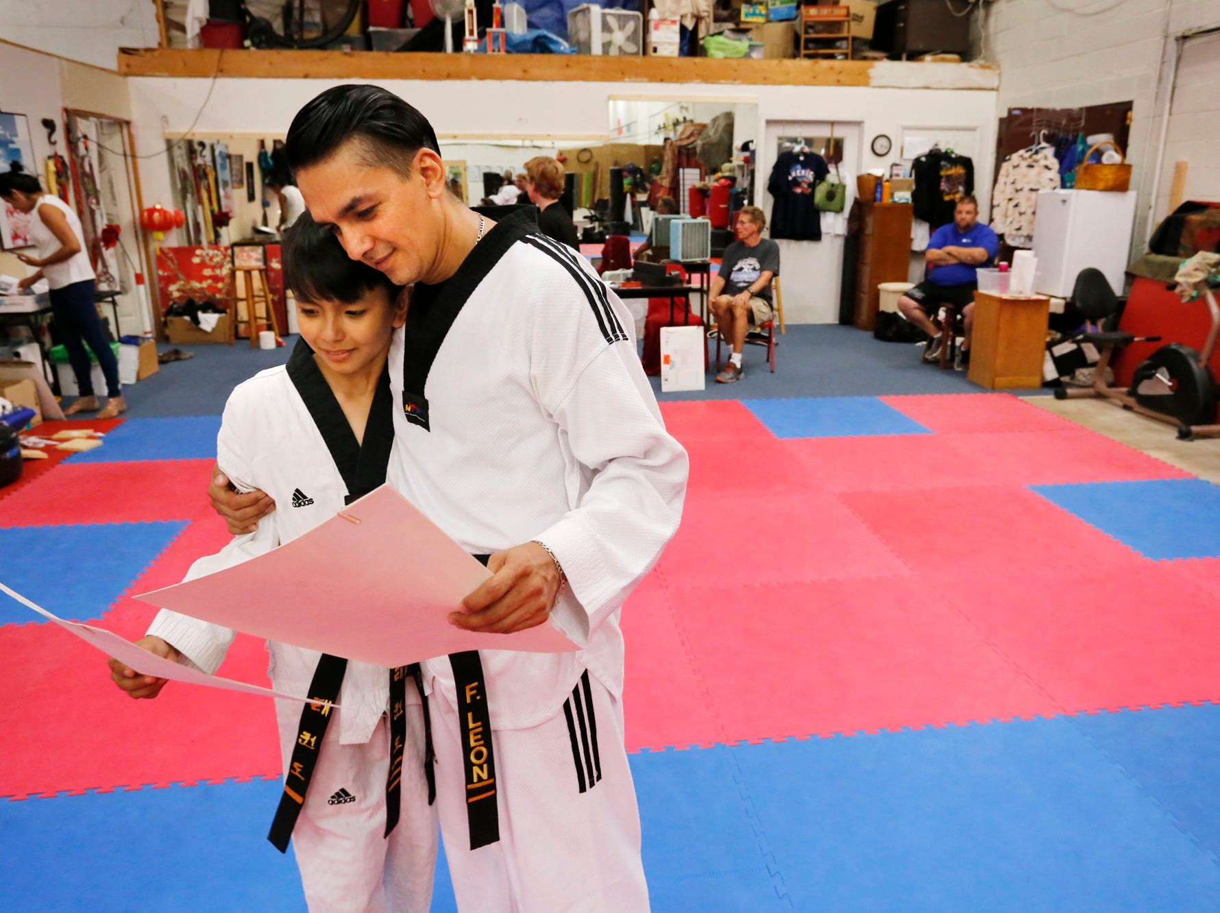 Felipe Leon embraces his son, Brandon, after they were both awarded their Dan certificates after passing the respective tests in Taekwondo at American House of Martial Arts Tuesday, August 28, 2018, inside Trader Buck's Flea Market, 2330 Sagamore Parkway South in Lafayette. Felipe Leon, 37, received is third Dan, or third degree black belt, in Taekwondao. Brandon received his one Dan, or first degreee black belt.