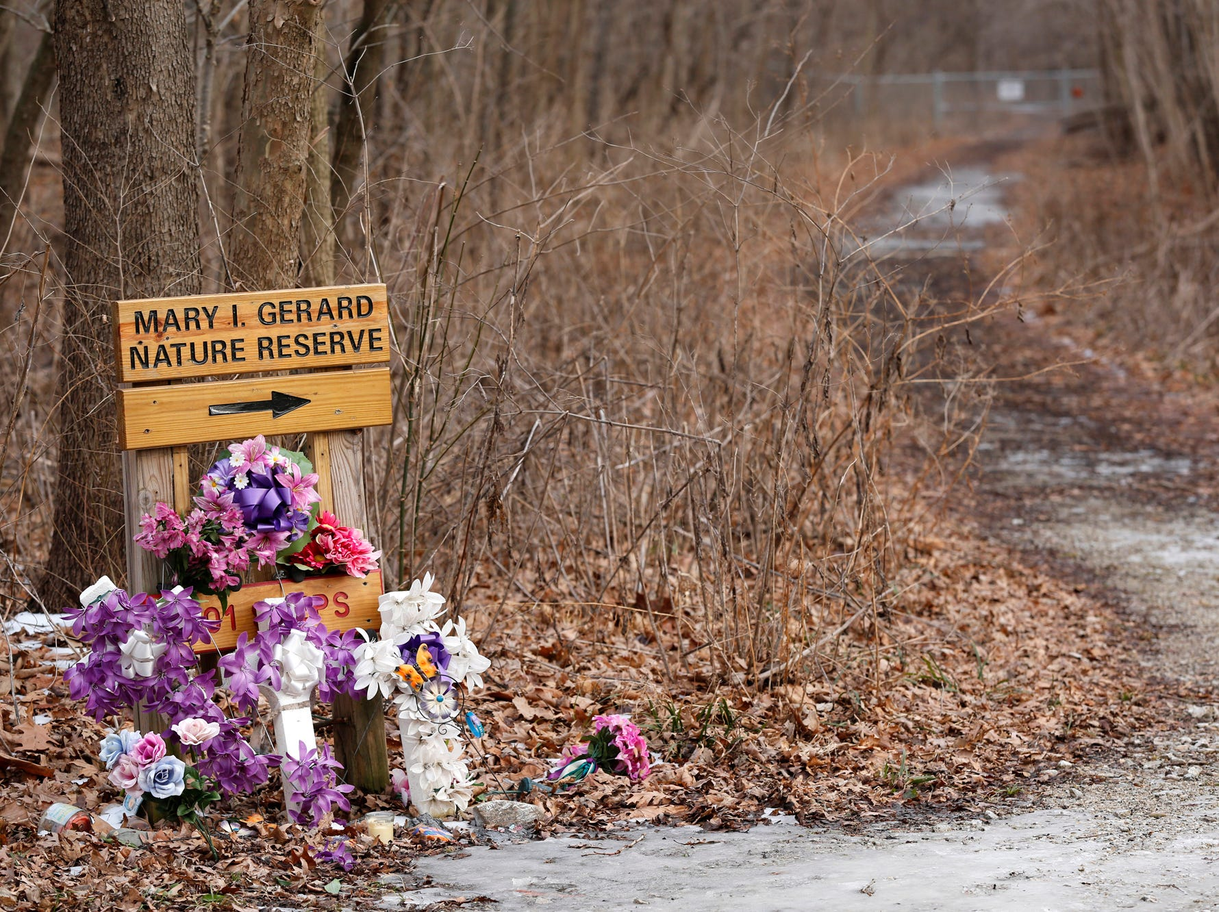 Flowers in memorial to Liberty German and Abigail Williams Tuesday, February 13, 2018, at the trail head of the Monon High Bridge Trail just east of Delphi. German and Williams were murdered February 13, 2017, as they hiked the Monon High Bridge Trail.