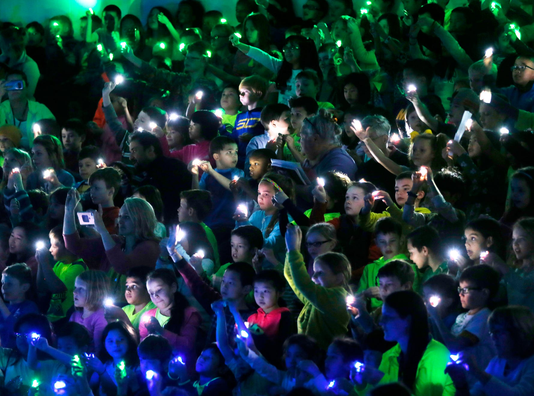 Students shine lights simulating fireflies as they greet Gov. Eric Holcomb Friday, March 23, 2018, at Cumberland Elementary School in West Lafayette. Gov. Holcomb came to the school to sign a bill naming the Say's Firefly as the Indiana state insect.
