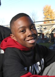 Ki'Anthony Tyus, 10, sat in the Shawnee neighborhood. He is part of the Hood 2 Hood campaign to end violence in the community.  Tyus survived being shot earlier this year by bullets meant for someone else.