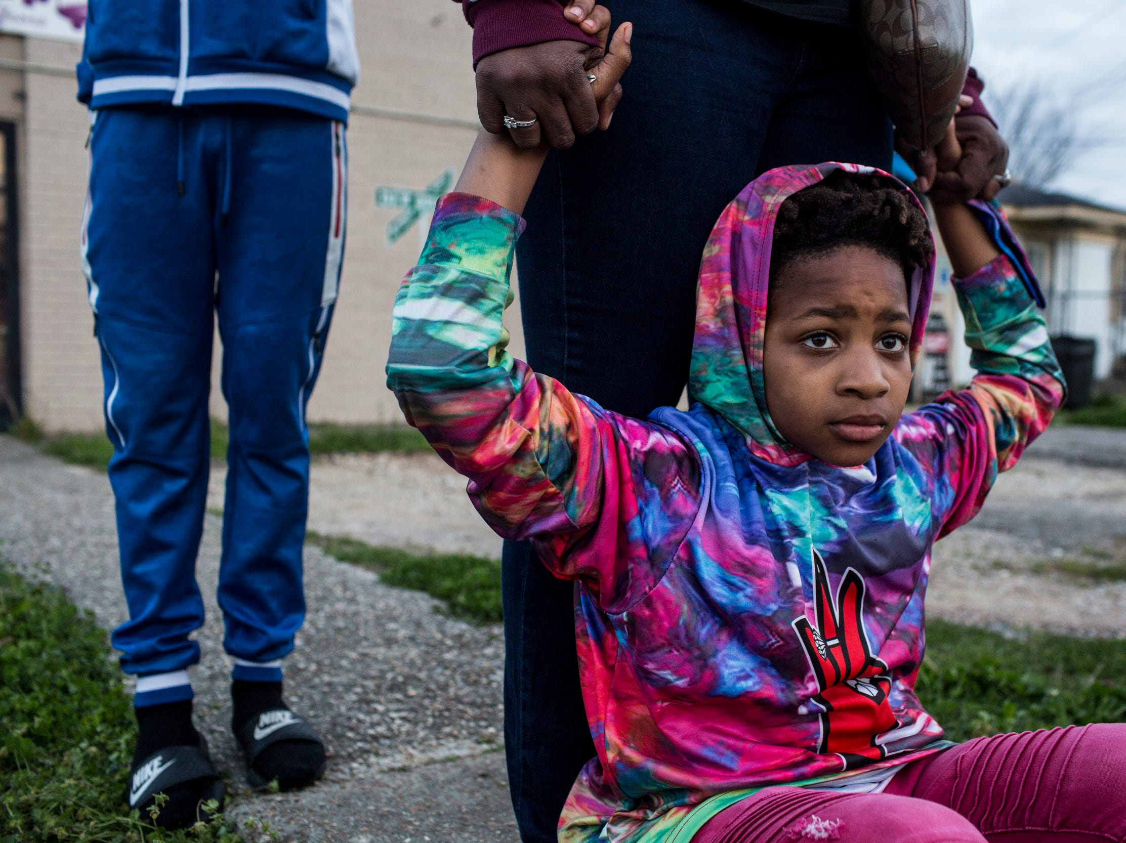 """April 02, 2018 -  Dominique Carpenter grasps onto Kendarius Carpenter, 10, her son, while watching neighbors who had gathered near Top Stop Shop in North Memphis. A clerk is accused of fatally shooting 17-year-old Dorian Harris after he stole a beer from the shop. """"It's just really disheartening,"""" Carpenter said. """"Stealing is wrong, yes. Should he be punished? Yes. But it didn't warrant death. That's why I'm out here."""""""