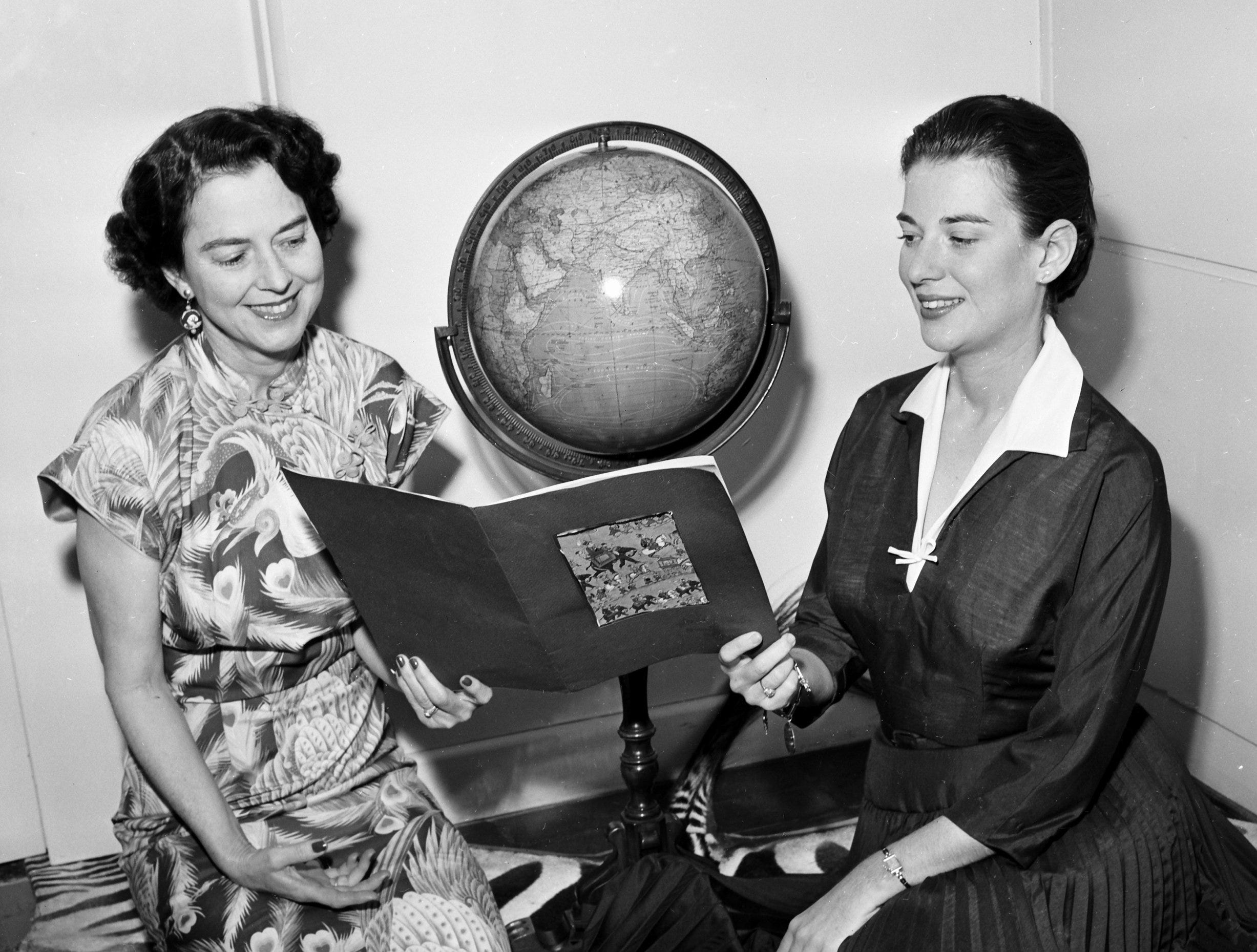 A four-month flight around the world is ahead for Mrs. Berry B. Brooks (Left) and her daughter, Miss Virginia Brooks, of Memphis.  Here they are brushing up on their knowledge of the orient, even sitting Japanese fashion while looking through travel articles on 17 Jan 1956.