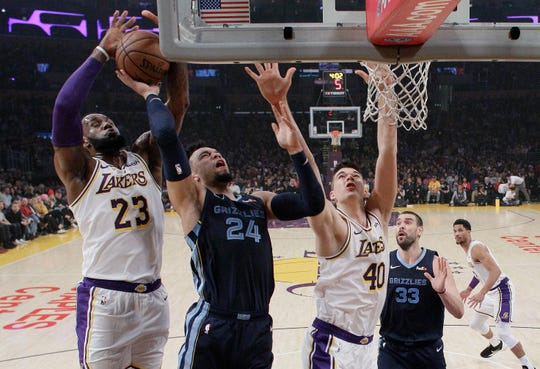 Memphis Grizzlies' Dillon Brooks (24) drives to the basket as Los Angeles Lakers' LeBron James (23) and Ivica Zubac (40) defend during the first half of an NBA basketball game, Sunday, Dec. 23, 2018, in Los Angeles. (AP Photo/Marcio Jose Sanchez)