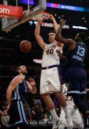 Los Angeles Lakers' Ivica Zubac (40) dunks between Memphis Grizzlies' Marc Gasol, left, and Jaren Jackson Jr. (13) during the first half of an NBA basketball game Sunday, Dec. 23, 2018, in Los Angeles. (AP Photo/Marcio Jose Sanchez)