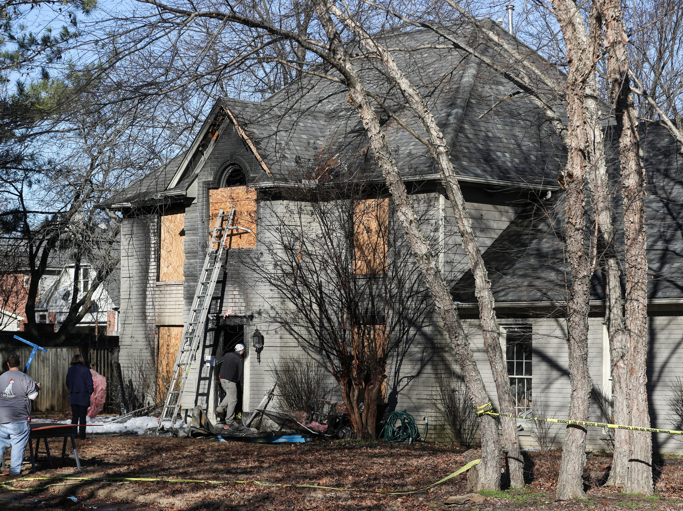 People work to board up the home on Autumn Winds Drive in Collierville on Dec. 24, 2018, after an overnight fire on Christmas Eve killed four people and injured four others.
