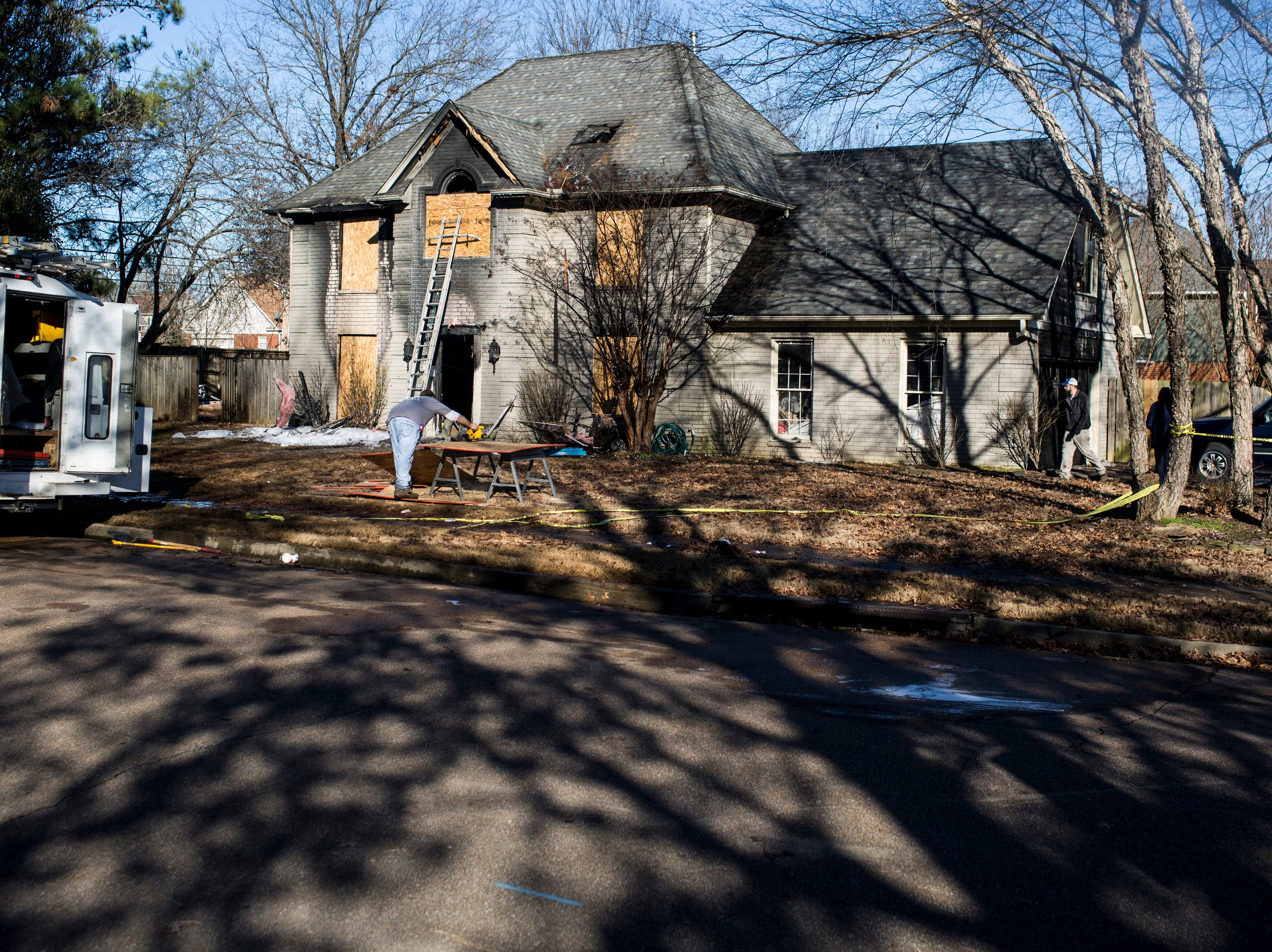 December 24 2018 - People work to board up the home on Autumn Winds Drive in Collierville after a overnight fire on Christmas Eve killed four people and injured four others.
