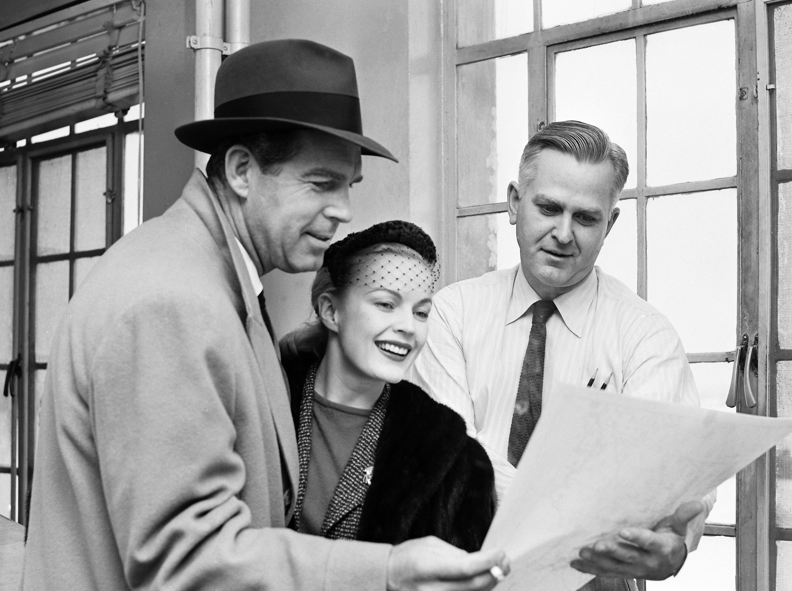 A snow-enforced delay on 23 Jan 1956 at Municipal Airport gave Hollywood star Fred MacMurray (Left) and his wife, June Haver, a former Memphian, the chance to check weather reports with James C. Hicks of 3060 Carnes, an aviation forecaster.