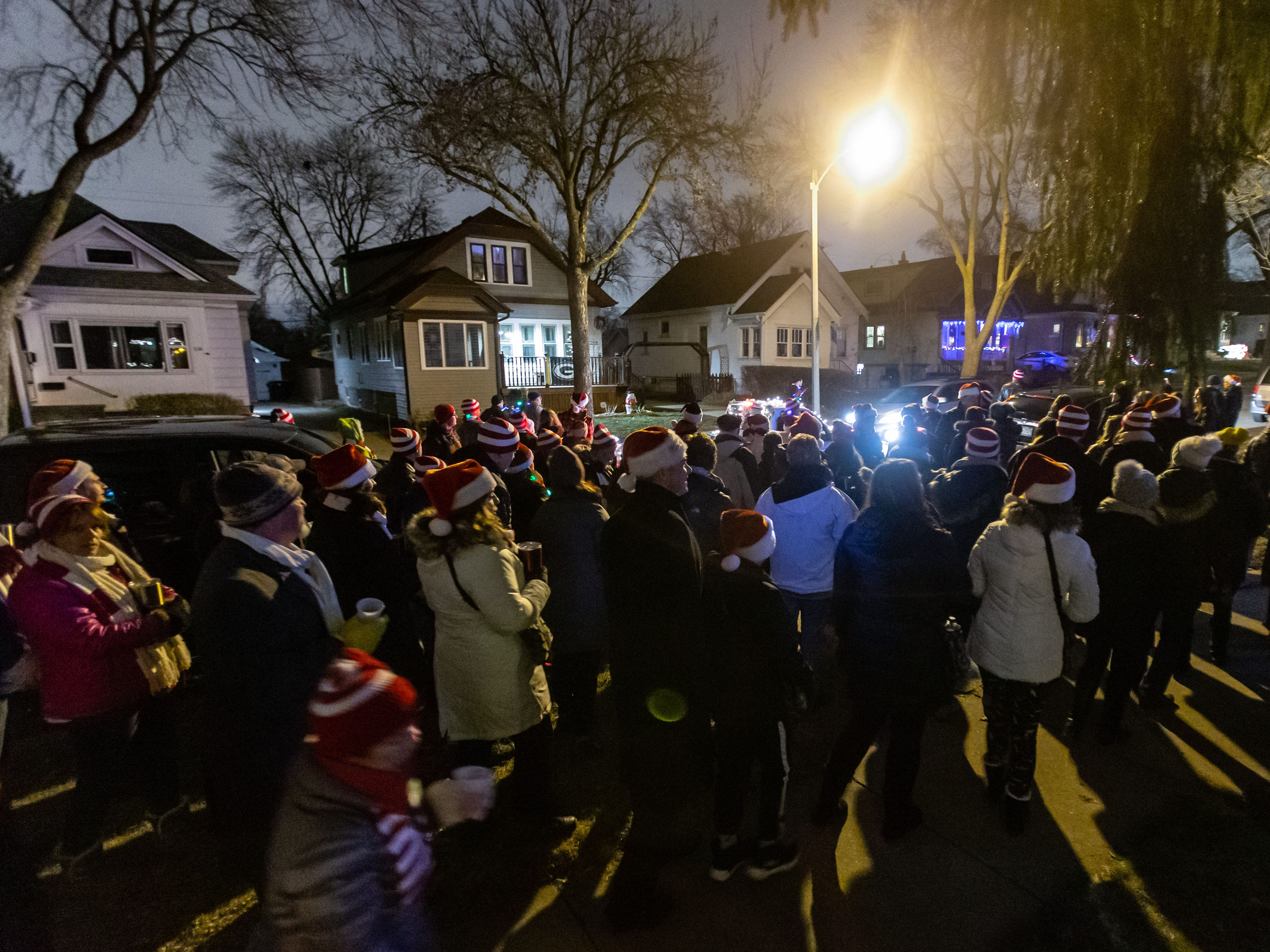 More than one hundred carolers march down 70th St. in Wauwatosa during Tosa's 7th Annual Christmas Caroling Extravaganza on Saturday, Dec. 22, 2018. The objective of the event is to spread holiday cheer and warm the winter night with song and folly.
