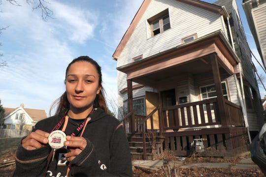Delilah Danowski, a member of the Wisconsin Air National Guard and volunteer with Habitat for Humanity, stands in front of the house at 1908 N. 29th St. in Milwaukee where her 11-year-old cousin Rita Martinez was killed by a stray bullet 20 years ago.