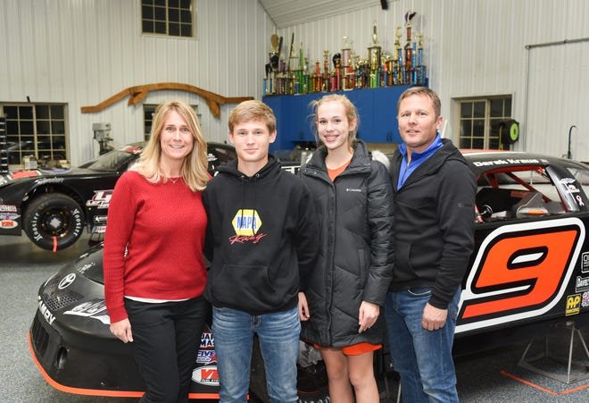 Stock-car driver Derek Kraus (second from left) poses with (from left) his mother, Kathy; sister, Lauren; and father, Mark, Tuesday, December 11, 2018, at their team's shop near their home on outside Stratford, Wisconsin.