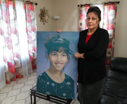 Cynthia Schulz holds a large portrait of her daughter Rita Martinez made from a school photo by co-workers after the 11-year-old was killed in 2000 by a stray bullet while sitting in her grandparents' Milwaukee home.