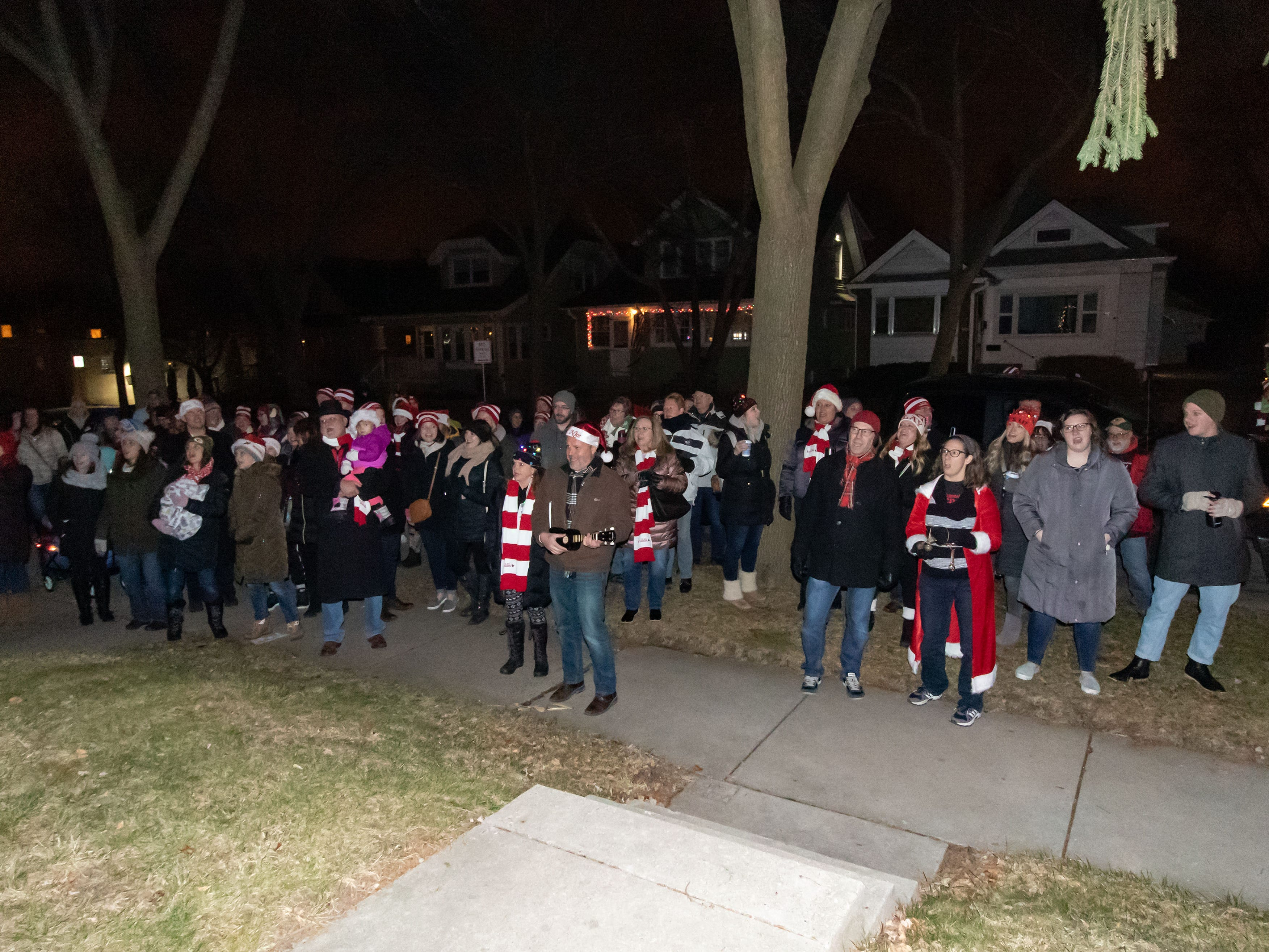 More than one hundred carolers stop to sing at a home on 70th St. in Wauwatosa during Tosa's 7th Annual Christmas Caroling Extravaganza on Saturday, Dec. 22, 2018. The objective of the event is to spread holiday cheer and warm the winter night with song and folly.