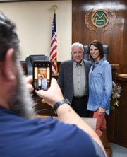 Council member-elect Bob Van Haaren takes a picture of outgoing Mayor Joe Dillard and his daughter, council member-elect Paige Evans, after the City Council's final meeting of the year on Dec. 20.