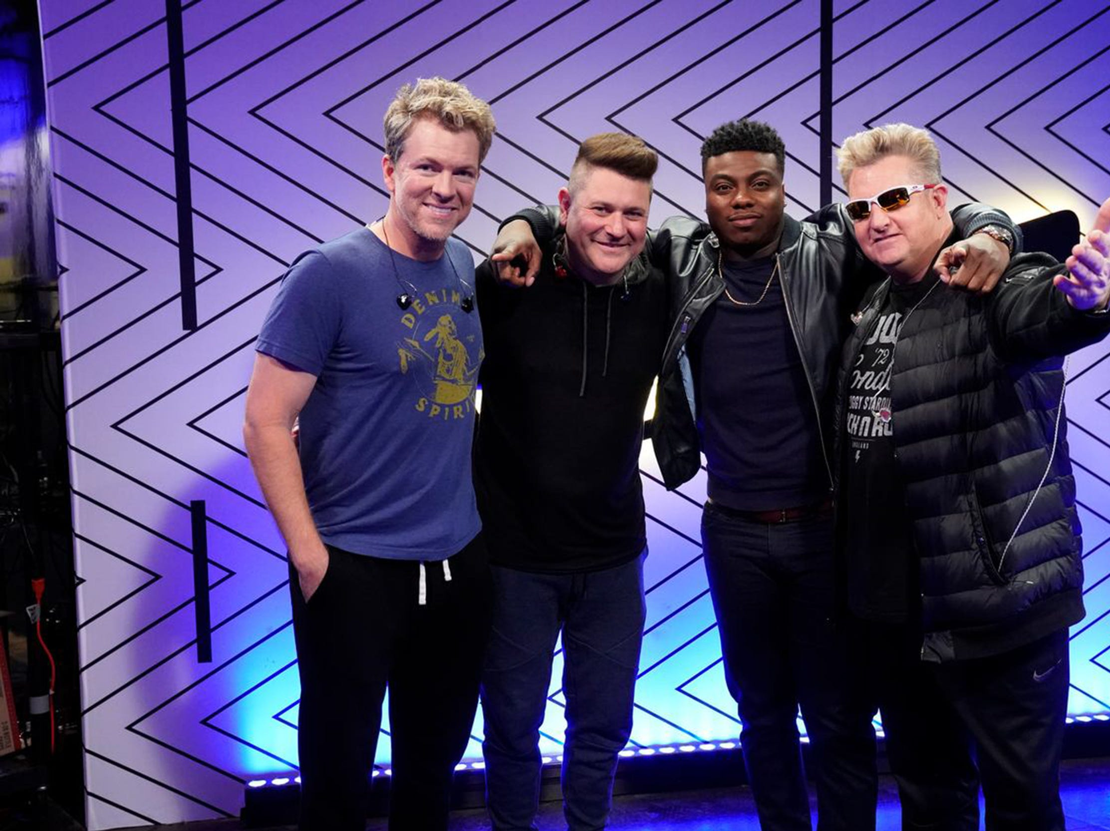 "Kirk Jay poses with the country group Rascal Flatts on Tuesday, Dec. 18, 2018, during the finals results show of ""The Voice."""