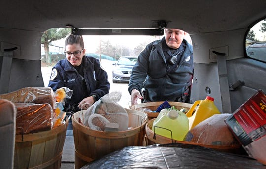 MNPD officers Rickie Corman and Brian Penny prepare to distribute food and gifts from the Christmas Basket Program to a family in need Monday Dec. 24, 2018, in Nashville, Tenn.