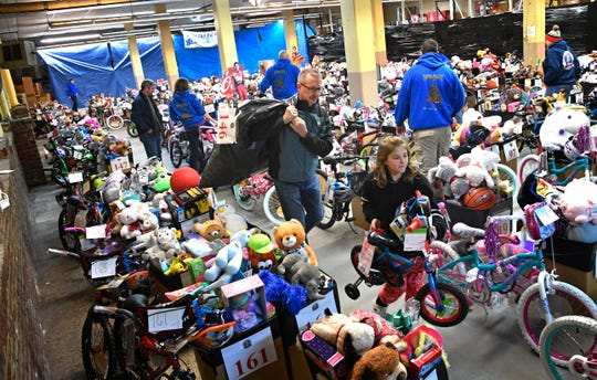 Jim Hooper carries a bag of toys while Aubrey Huggins rolls a bike to be delivered to a needy family  Monday Dec. 24, 2018, in Nashville, Tenn.Over 700 Nashville children received gifts of toys from MNPD officers on Christmas Eve morning as the police department celebrates the 58th anniversary of the Christmas Basket Program for needy families. The children are part of more than 240 families who live throughout Nashville.