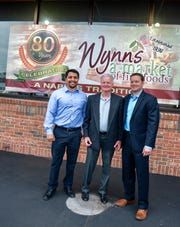 Juan Padilla, assistant store manager at Wynn's Market, (left), stands with Tim Wynn, president of Wynn's Market (center) and his son, Jeff Wynn (right), president of Wynn Properties.