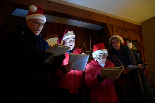 (from left) Patrick Finley, George Dakes, Carol Dakes, and Christine Finley sing carols during a Christmas party on Sunday, Dec. 23, 2018, in Ho-Ho-Kus.