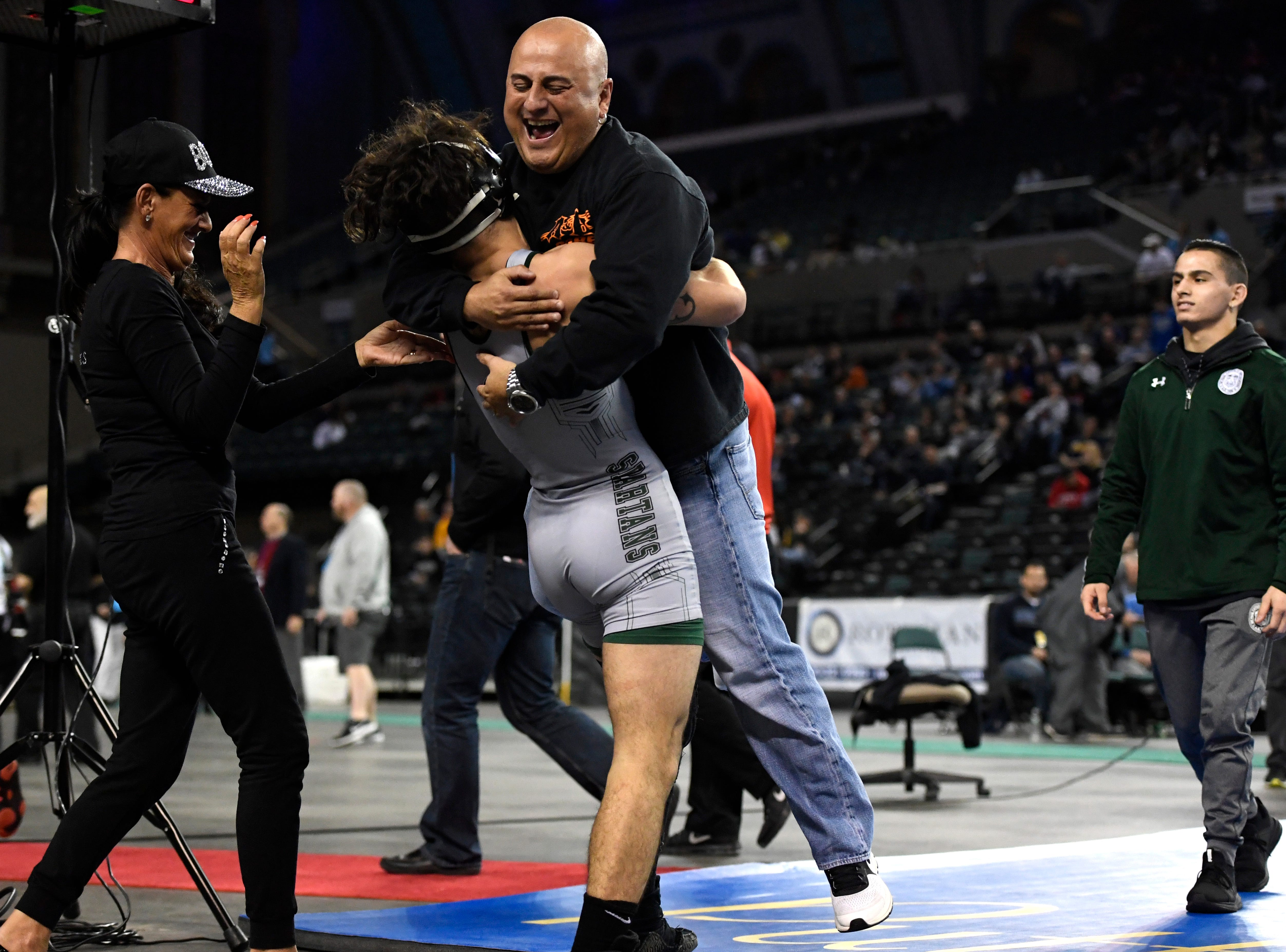 DePaul's Ricky Cabanillas lifts his father Carlos Cabanillas after winning the 145-pound title during the NJSIAA state wrestling championships in Atlantic City, NJ on Sunday, March 4, 2018.