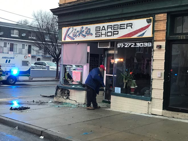 Glass and cement is strewn across the sidewalk in front of a Garfield barber shop following an accident Dec. 24, 2018.