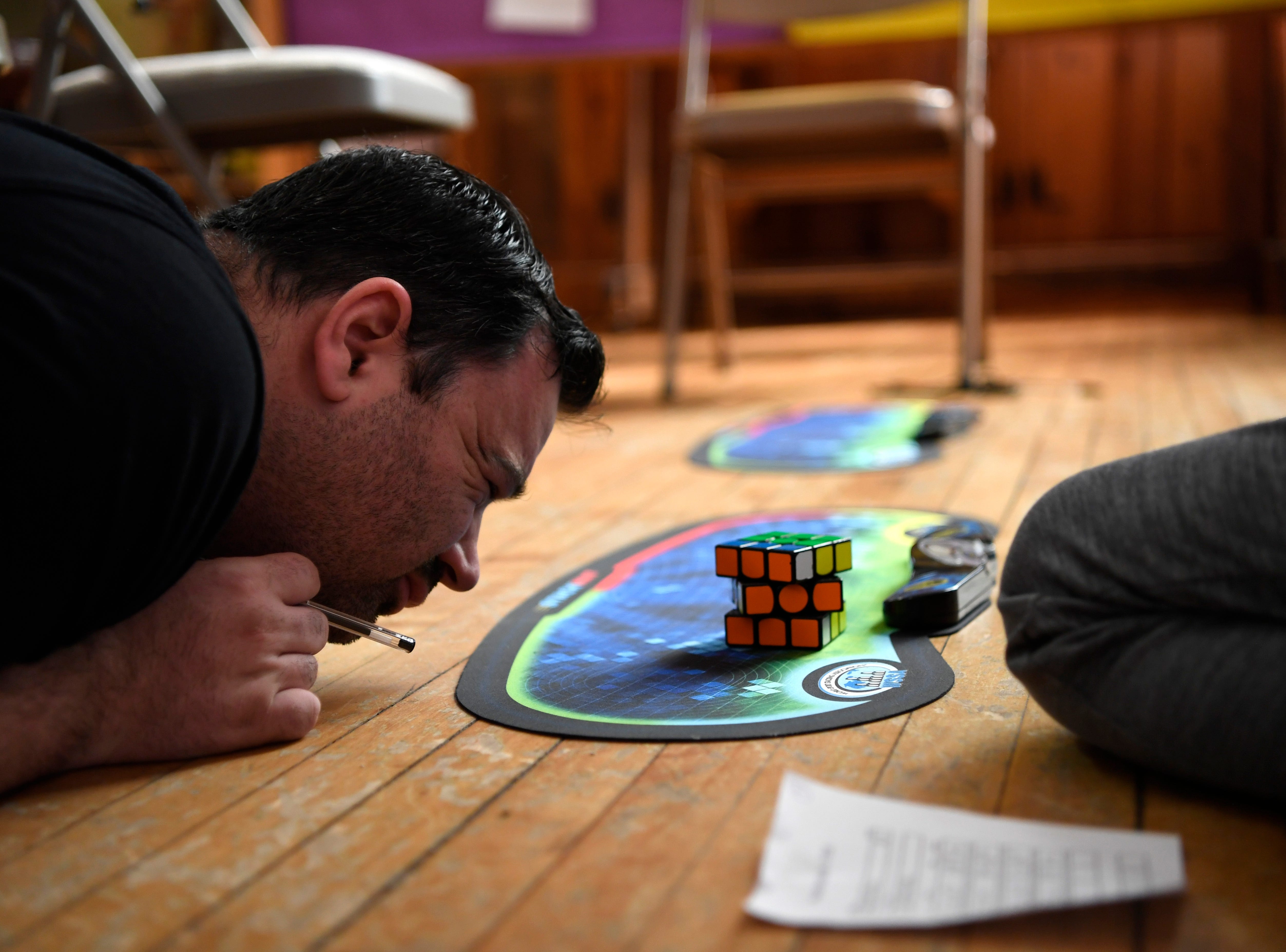 World Cube Association delegate Bob Burton closely inspects a cube during the 3x3x3 cube with feet competition in Rutherford, NJ on Saturday, June 9, 2018.