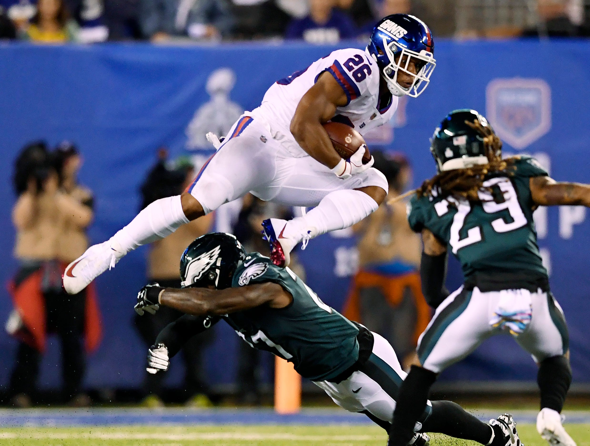New York Giants running back Saquon Barkley (26) jumps over an Eagles defender in the first half. The New York Giants face the Philadelphia Eagles on Thursday, Oct. 11, 2018, in East Rutherford.