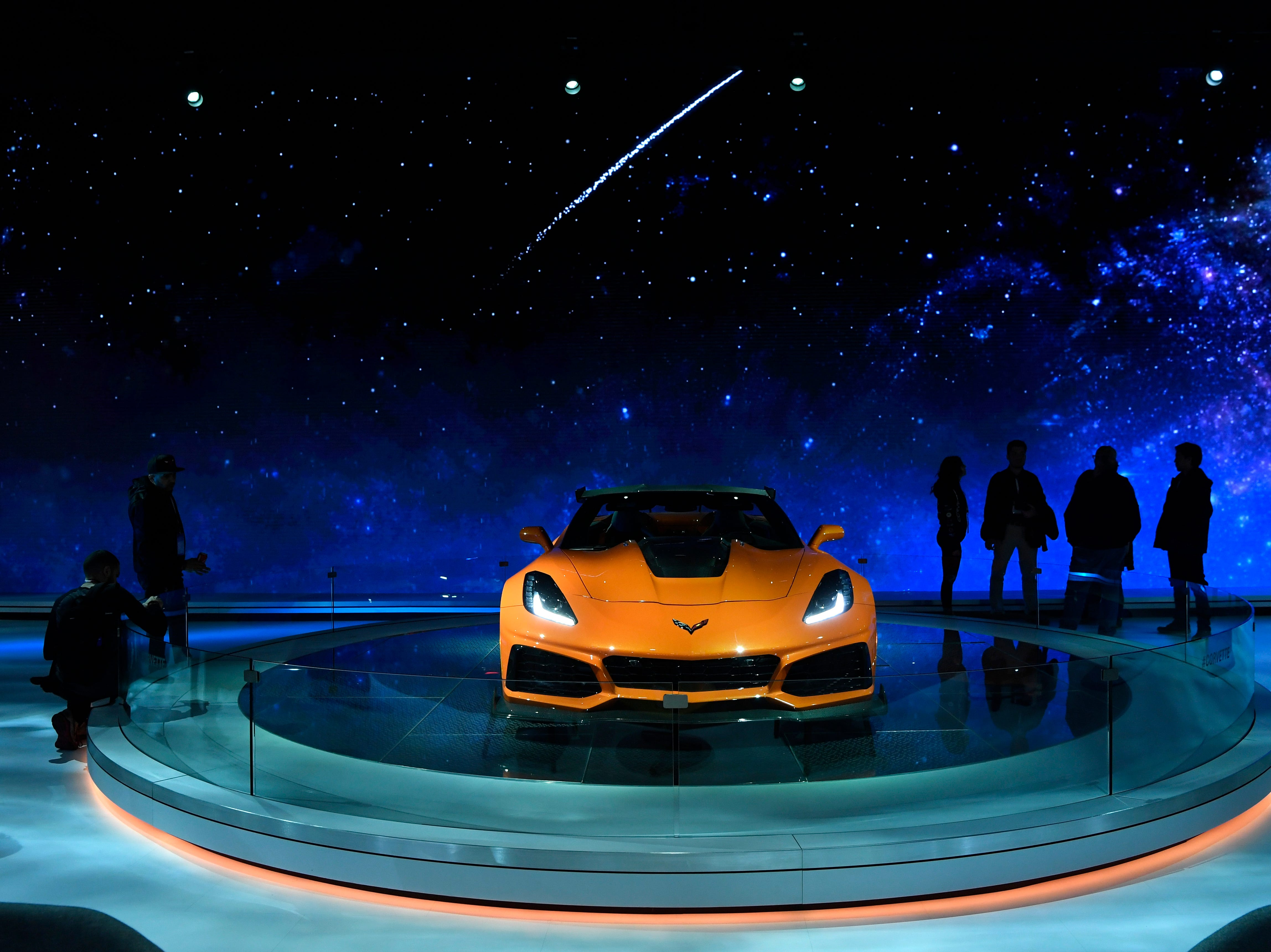 People stand around the 2019 Chevy Corvette on display during the New York International Auto Show on Wednesday, March 28, 2018.