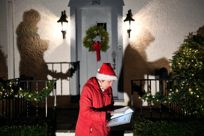 Carol Dakes looks over her book of carols before singing with her group on Sunday, Dec. 23, 2018, in Ho-Ho-Kus.