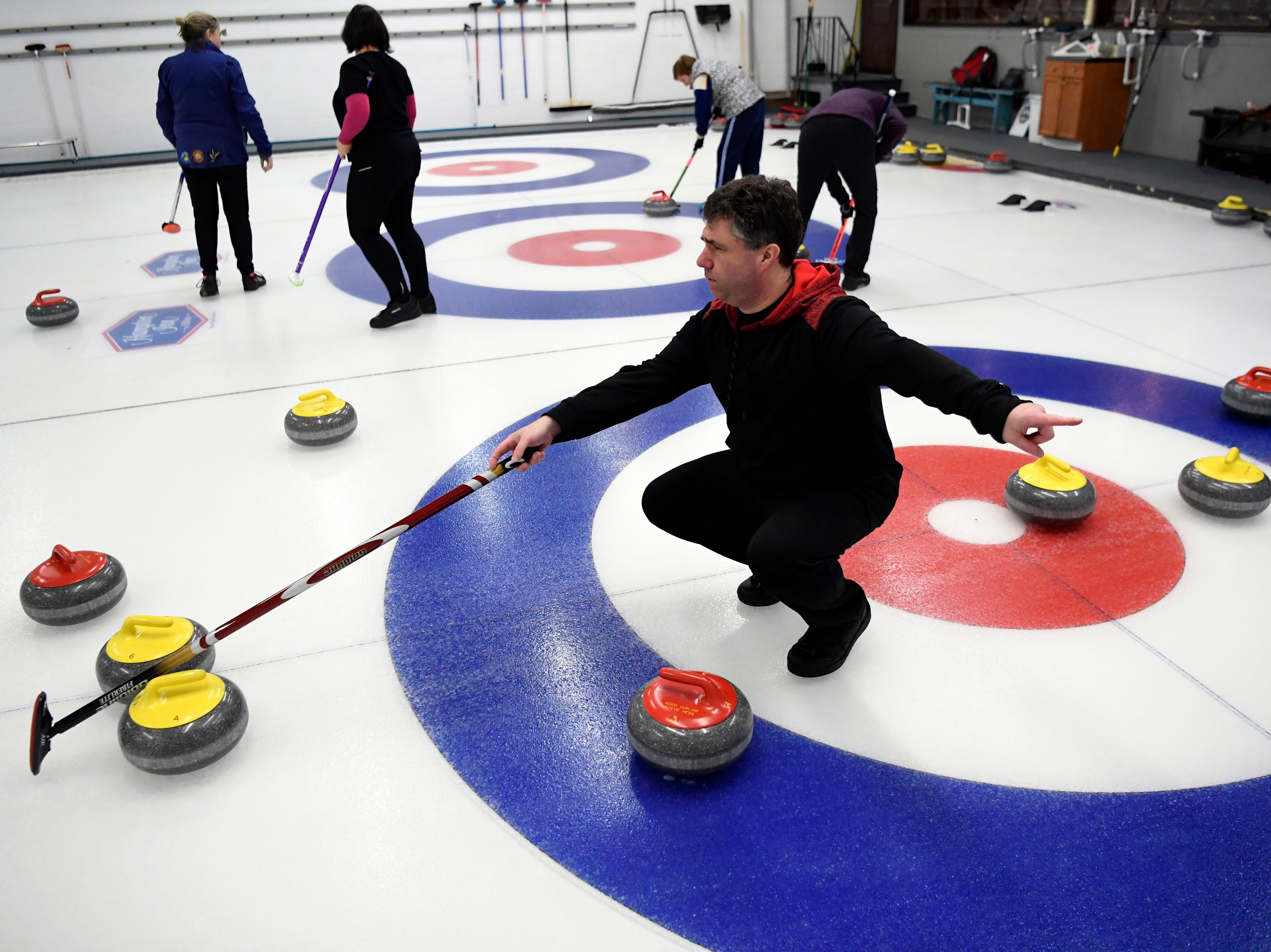 Joe Angelli, foreground, of Hackensack, signals to his thrower during a curling match in the Ardsley Curling Club on Tuesday, January 16, 2018.