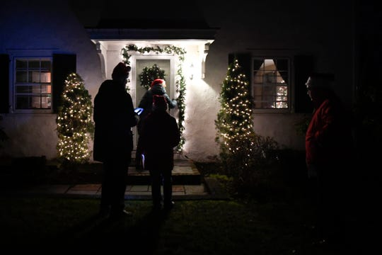 Christine Finley rings the doorbell as (from left) Patrick Finley, Carol Dakes, and George Dakes wait to sing carols  on Sunday, Dec. 23, 2018, in Ho-Ho-Kus.