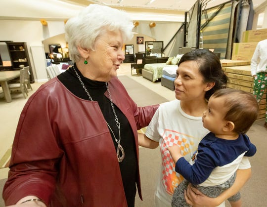 Perla Rivera and her son Matthew Hernandez, 1, both of Las Cruces, greet and thank Ashely Furniture HomeStore owner Wanda Bowman on Sunday, Dec. 23, 2018 after receiving a new twin-size bed and mattress.