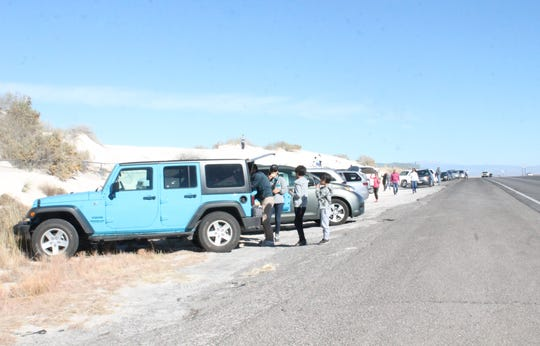 Visitors park alongside US 70, ready to hop a fence into White Sands National Monument, which is closed because of the government shutdown.