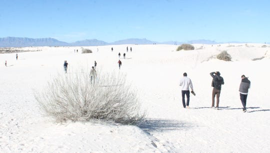 Visitors take off their shoes Dec. 24, 2018, to enjoy White Sands National Monument near Alamogordo, New Mexico, despite the park being closed because of the government shutdown.