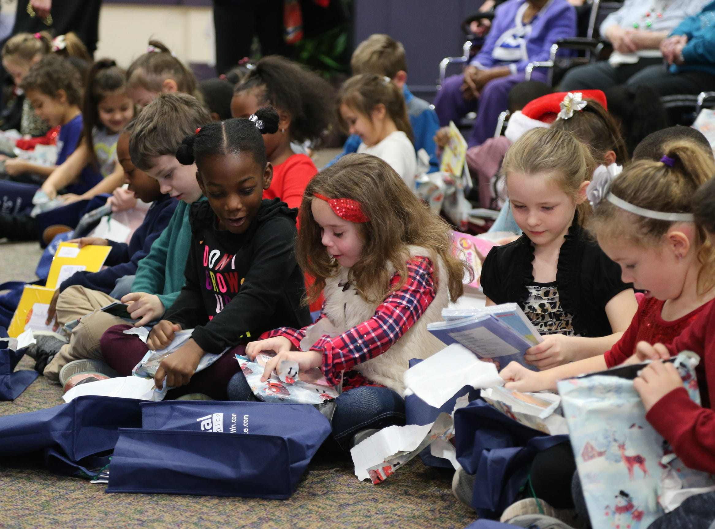 First-grade students from Botsford Elementary excitedly open gifts of books from residents and staff at Botsford Commons.