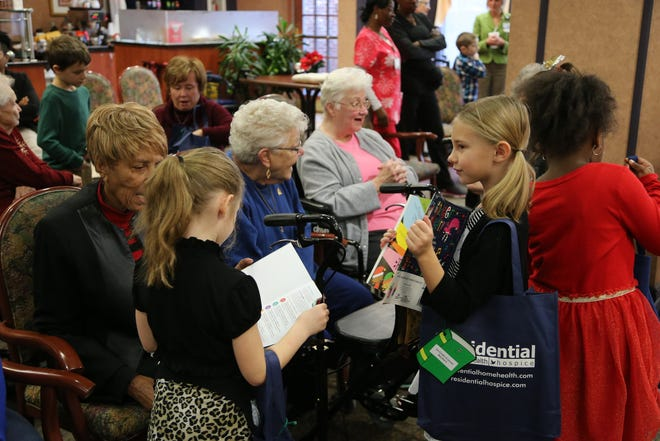 Children visited with residents to share their new books during the Giving Tree.