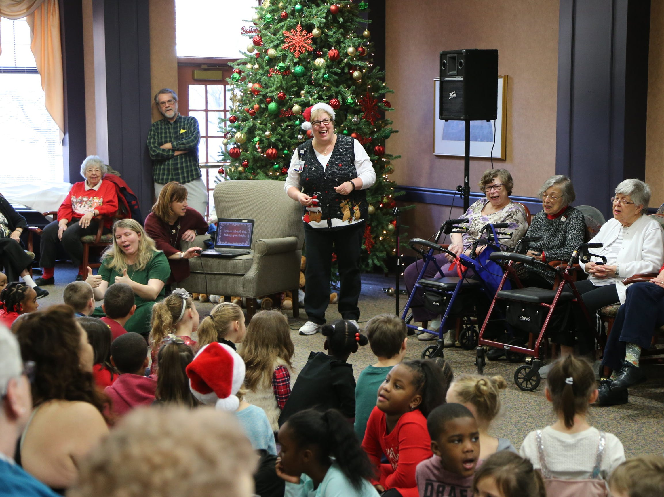 Barb Smith, Fullness of Life coordinator at Botsford Commons, helps lead senior residents and first-graders from Botsford Elementary in the singing favorite holiday songs.
