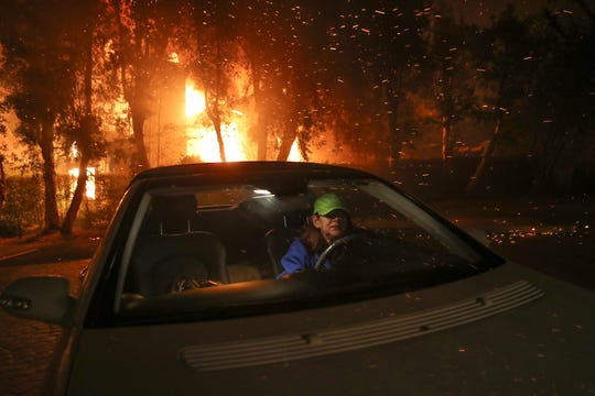 Tina Weeks jumps into her car to evacuate after her neighbor's house became fully engulfed by a California wildfire in Oak Park, Calif. on November 9, 2018.