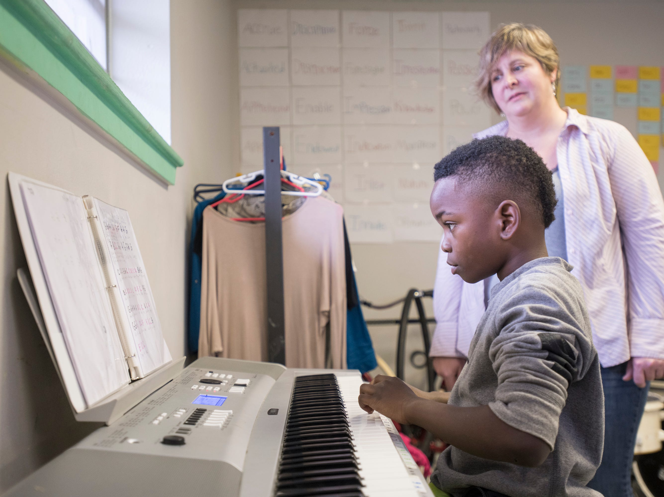 """Volunteer teacher Joy Weirick looks on as Christopher """"CJ"""" Williams, 9, practices the piano at the Robinson Harris Academy of Music in Pensacola on Friday, December 21, 2018."""