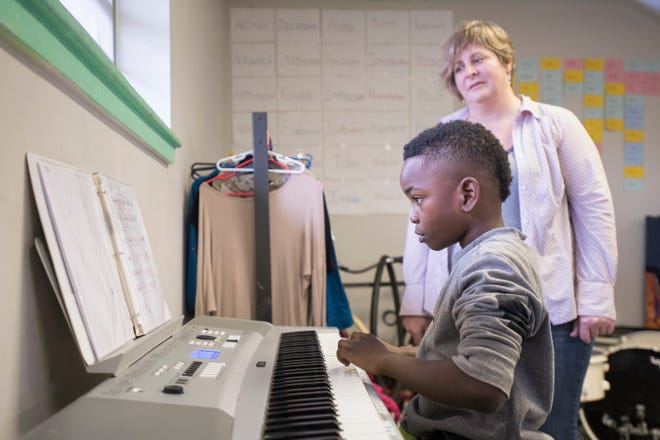 "Volunteer piano instructor Joy Weirick looks on Friday as Christopher ""CJ"" Williams, 9, practices the piano at the Robinson Harris Academy of Music in Pensacola."