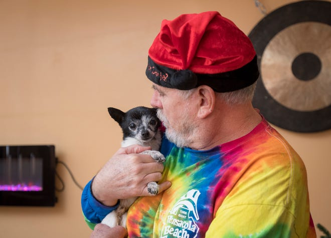 John Harding, a volunteer with the Friends of the Escambia County Animal Shelter fospice program, hugs 10-year-old Chihuahua mix Miguel on Friday at his home in Pensacola.