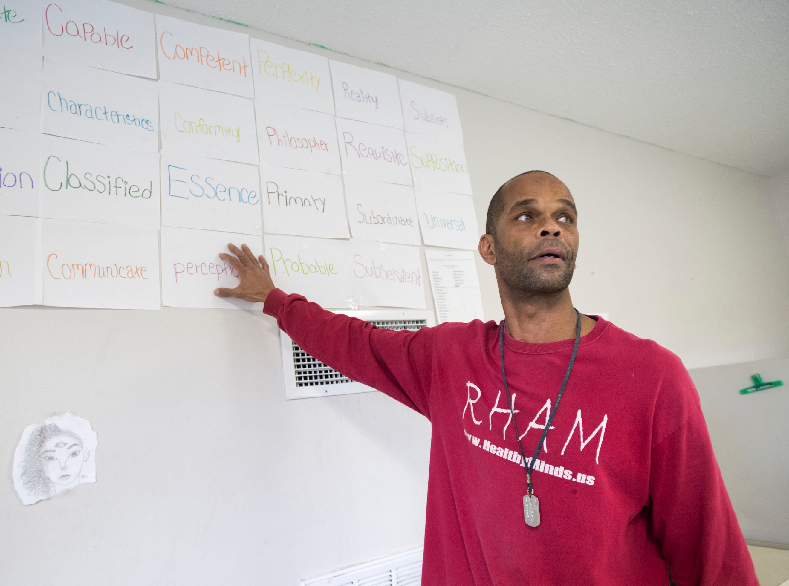 Pierre Robinson points out vocabulary words from Aristotle's Metaphysics that he has hung on the wall as part of  his Robinson Harris Academy of Music in Pensacola on Friday, December 21, 2018.