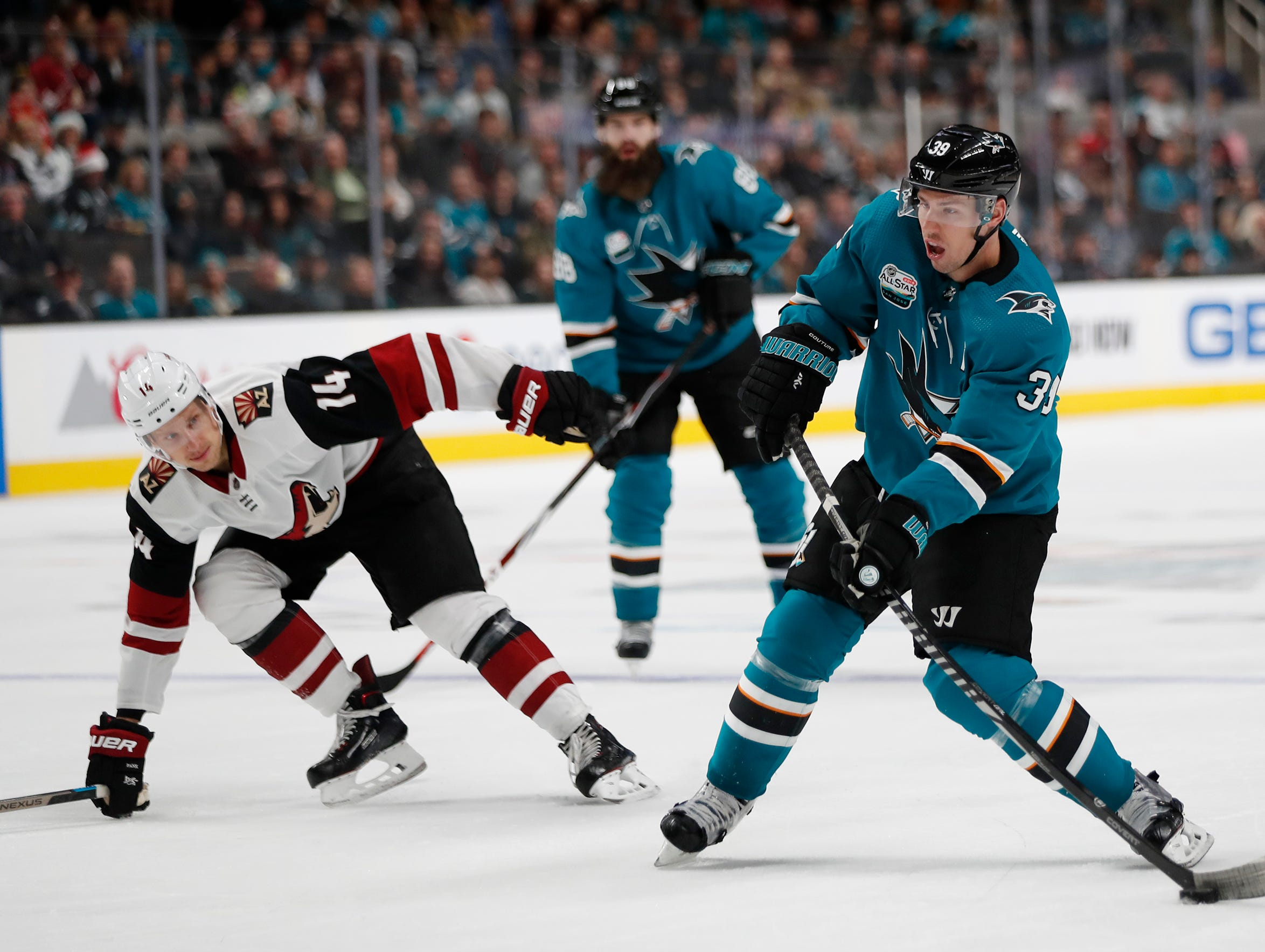 San Jose Sharks' Logan Couture (39) shoots the puck against the Arizona Coyotes' Richard Panik (14) in the first period of an NHL hockey game in San Jose, Calif., Sunday, Dec. 23, 2018. (AP Photo/Josie Lepe)