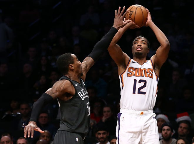 Dec 23, 2018; Brooklyn, NY, USA; Phoenix Suns forward T.J. Warren (12) puts up a shot against Brooklyn Nets forward Rondae Hollis-Jefferson (24) in the second quarter at Barclays Center. Mandatory Credit: Nicole Sweet-USA TODAY Sports