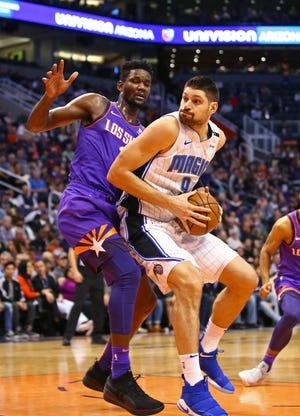 Magic center Nikola Vucevic works against Suns center Deandre Ayton during the first half of a game Nov. 30 at Talking Stick Resort Arena.