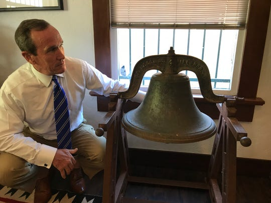 Lobbyist Kevin DeMenna poses with the Lees Ferry bell, which is being stored in his office near the Arizona Capitol.