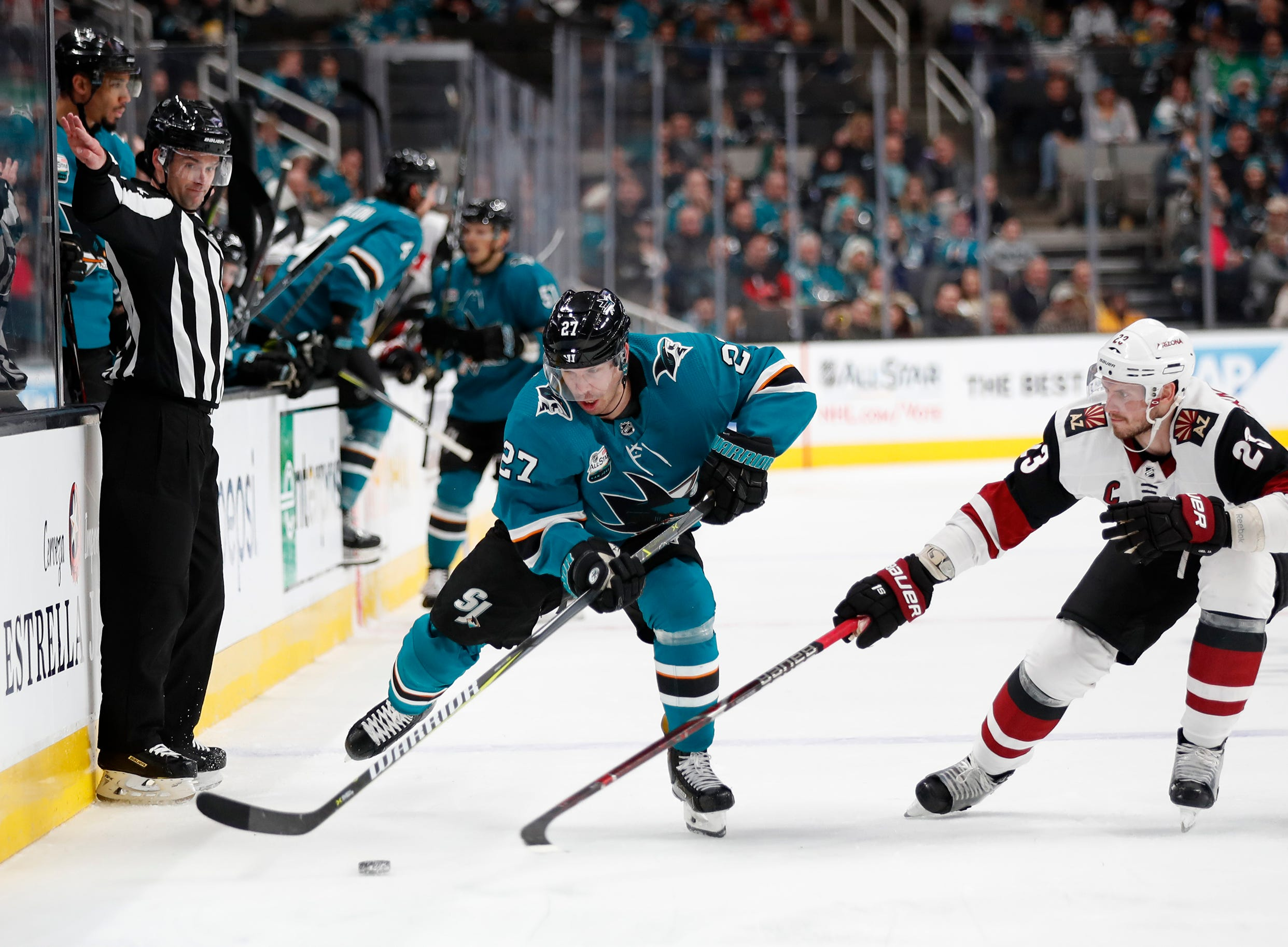 San Jose Sharks' Joonas Donskoi (27) battles for the puck against the Arizona Coyotes' Oliver Ekman-Larsson (23) in the second period of an NHL hockey game in San Jose, Calif., Sunday, Dec. 23, 2018. (AP Photo/Josie Lepe)