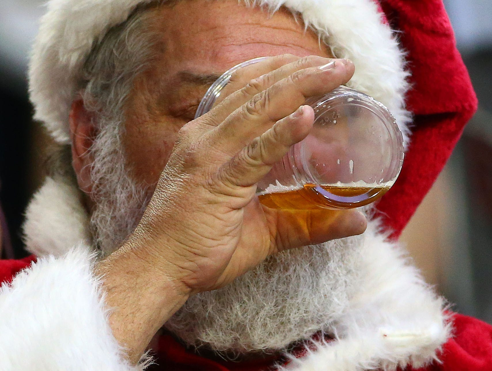 A fan dressed as Santa finishes-off a beer late in the fourth quarter as the Arizona Cardinals are defeated 31-9 by the Los Angeles Rams during the final home game of the season on Dec. 23 at State Farm Stadium.
