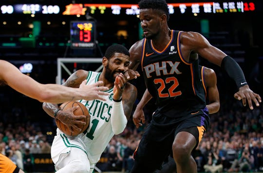 Celtics guard Kyrie Irving drives to the basket against Suns rookie Deandre Ayton during the second half of a game Dec. 19 at TD Garden.