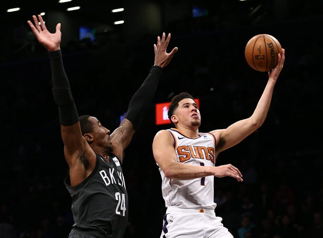 Dec 23, 2018; Brooklyn, NY, USA; Phoenix Suns guard Devin Booker (1) puts up a shot against Brooklyn Nets forward Rondae Hollis-Jefferson (24) in the first quarter at Barclays Center. Mandatory Credit: Nicole Sweet-USA TODAY Sports